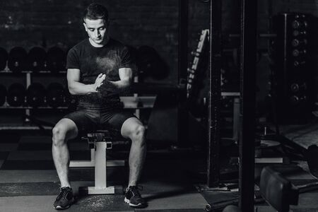 Beautiful handsome young athlete dressed in black t-shirt. During this time, sitting on the tires and applying talcum to your hands in the gym.