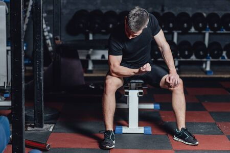 A young sportsman is sitting in a trunk hall. During this dress, wear a black T-shirt. Looking at your biceps hands. Stockfoto
