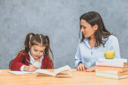 Young mother and daughter sitting on a gray background. During this, the mother watches over how a daughter performs a homework assignment. Stockfoto