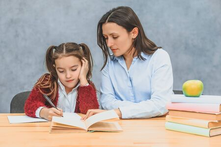 Mom helps daughter with homework on a gray background. During this they look into the notebook. Daughter writes carefully.