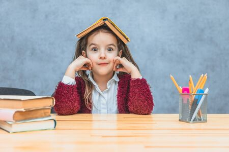 A cheerful girl sitting and holding a book over her head over a grey background. During this schoolgirl looks into the camera, putting his hands on his cheeks. Stockfoto
