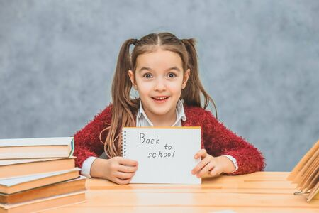 A little schoolgirl on a gray background. Hold text paper back to school. Look into the camera.