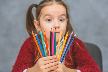 Close-up concept of colored pencils in the hands of the girl that holds them on the level of the face. Schoolgirl and pencil. Gray background. Look at the pencil. Red jacket.