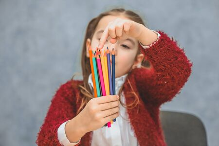 Close-up concept of colored pencils in one hand girls. Keeping them selects the right pencil. The gray background. The puppet looks at the pencil.