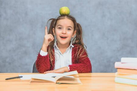 Portrait of cute clever girl with apple on her head. Sitting from a stack of books at the table, a copy of the space. Concept of education and development.
