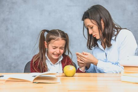 Mom talking to her baby. During this on a gray background. The girl cries, mom stroking her hand and talking to her daughter. Gray background. On the desk of the book and a green apple.