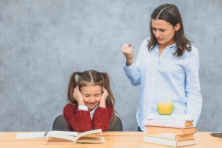 Mom and daughter on a gray background. At the same time mother quarreled with her daughter, shouting with a raised hand showing a fist. The schoolboy closed his eyes and ears with his hands.