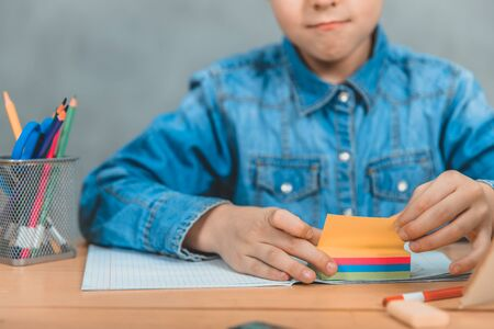 Learning process. Gray background. Crop, blurred, focus on the colorful stickers. Stockfoto