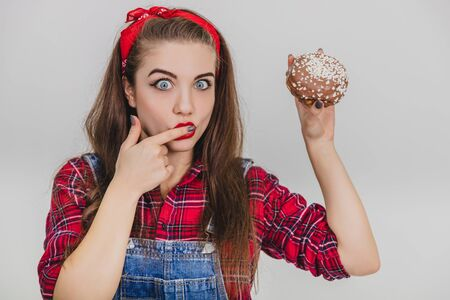 Lovely young female licking her finger sweet icing out of big chocolate doughnut.
