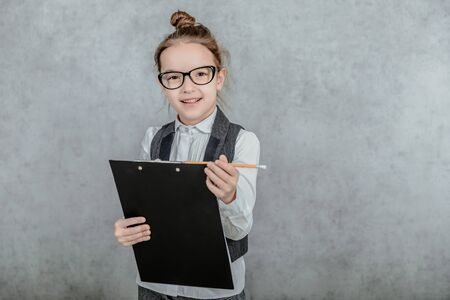 Little girl with pen and clipboard in her hands dressed as a businesswoman