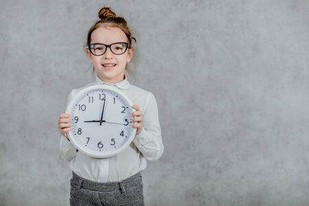 Portrait of a beautiful little brunette girl wearing a shirt holding hands clock isolated on a white background.