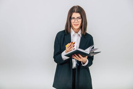 Pretty young businesslady in black suit standing, listening attentively, noting something in her notebook. Misunderstanding on her face.