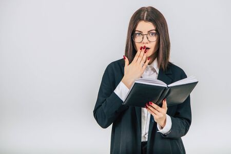 Successful young businesslady checking data in her notebook, thinking, covering mouth, shocked face expression.