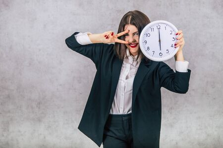 Pretty female employee raising white clock, smiling, showing peace sign.