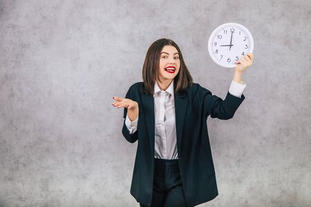 Pretty female employee raising up the white clock, smiling, happily, holding her hand as if she doesnt understand anything.