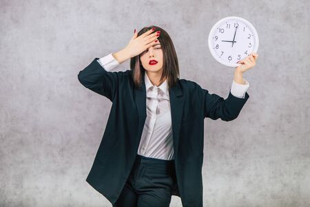 Pretty tired female employee raising up a clock, keeping hand on the head, looking ill, having headache.