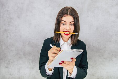 Funny business women standing with pencil in her teeth and writing down something into the notebook quickly.