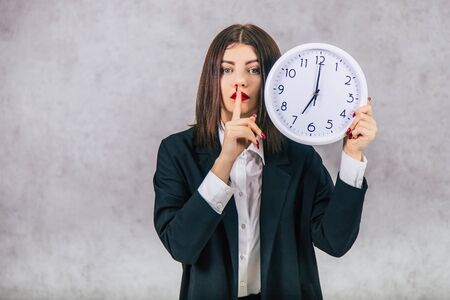 Pretty female employee raising up the white clock, showing silence sign.