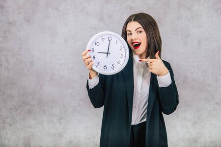 Pretty office female employee standing, pointing her finger at the clock in her hand.