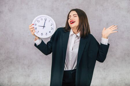 Pretty office female employee with clock in her hands, smiling, posing happily. Imagens