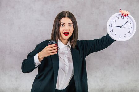 Pretty female employee raising up the white clock, smiling, happily, holding a cup of coffee, showing that it is time for coffee break at last. Imagens