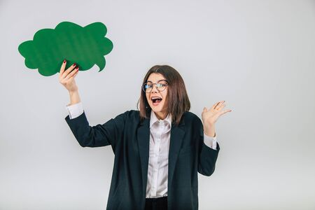 Lovely young businesslady standing with green cloud-like speech bubble, throwing her hand, looking shocked and amazed. Imagens