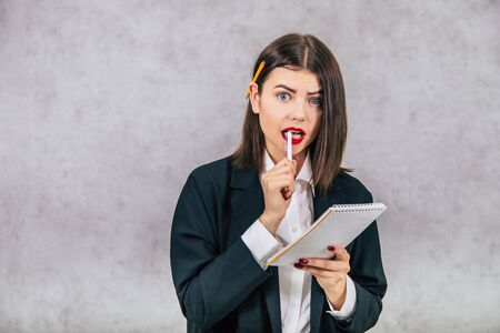 Cute business women standing with pencil behind her ear and puzzled, scared unconfident face expression, looking to the side, holding notebook, gnawing the pen.