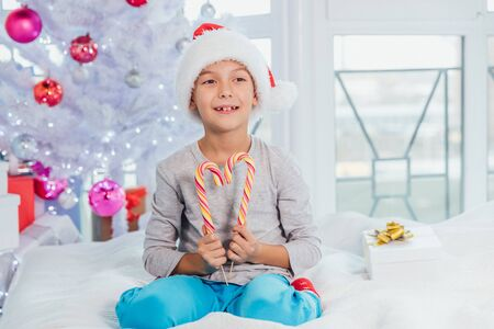 Funny boy in santa hat is sitting on the bed in pyjamas, demonstrating striped candy canes. Banque d'images - 132106508