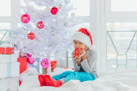Sleepy boy is drinking cocoa, sitting on the bed near christmas tree in the morning after the New Year.