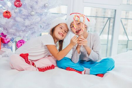 Adorable caucasian kids enjoy christmas morning, playing in bed, making heart from candy canes.