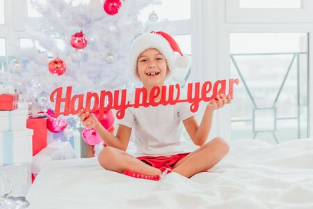 Happy little child, looking like santa, holding a paper text Happy New Year near the big Christmas tree. Banco de Imagens