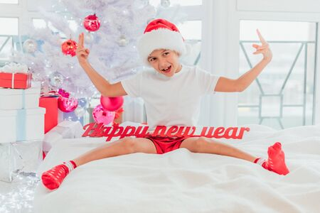Funny funky boy with red Happy New Year text, sitting on the white bed blanket near christmas tree, showing cool gesture,