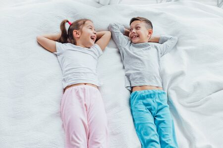 Top view on two beautiful siblings lying on a bed together, smiling while having a rest.