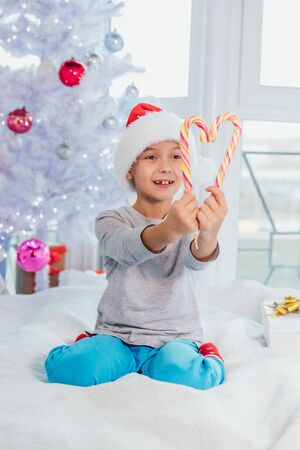 Funny boy in santa hat is sitting on the bed in pyjamas, demonstrating striped candy canes.