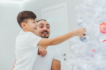 Dad and son decorate a christmas tree together