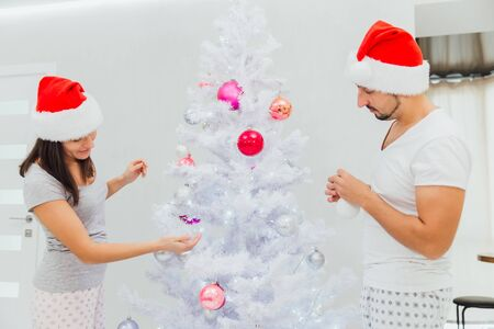Christmas tree decorating young couple putting on xmas balls on white tree together.