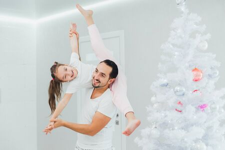 Father is playing with her little daughter near the Christmas tree at home, pastel colors decoration Stok Fotoğraf