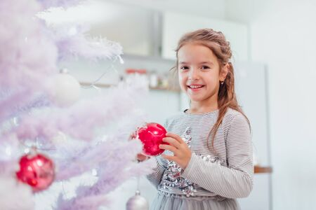 Little girl is totally fascinated by beautifully decorated christmas tree with lights and balls.