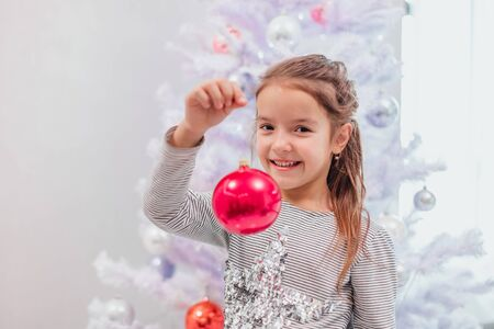 Small brunette girl is demonstrates a pink bauble, standing near Christmas tree, smiling. Stok Fotoğraf