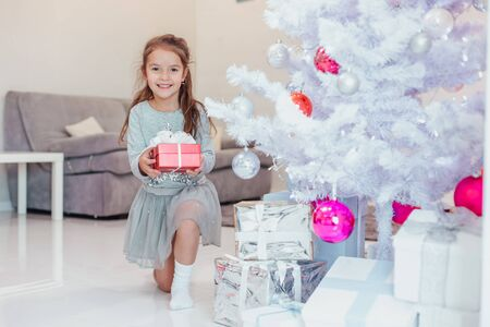 Lovely kid is preparing presents for winter holidays, putting them under the firtree.