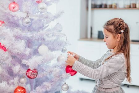 Small brunette girl is decorating a faux Christmas tree with colorful baubles at home.