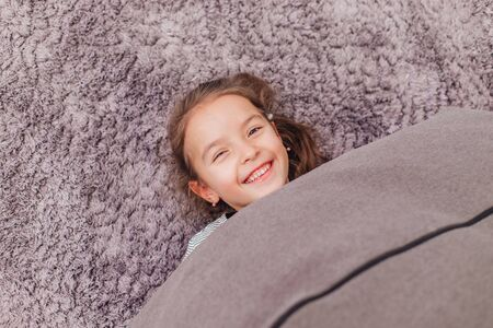 Laughing little girl hides under grey blanket, lying on the grey carpet, so that only her smiling face is seen.