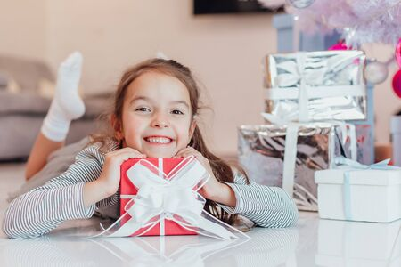 Closeup of beautiful little angel girl with perfect smile laying on the floor, keeping hands and chin on red present box with white bow. Stok Fotoğraf