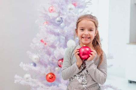 Little cutie is holding pink glass bauble close to her chest, showing how much pleasure decoration of christmas tree brings her. Stok Fotoğraf