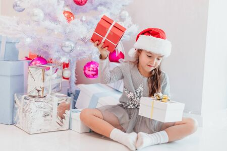 Young beautiful girl making choice between two gift boxes, sitting in the room decorated for christmas. Stok Fotoğraf