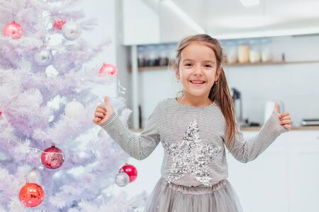 Small kid with funny is standing near christmas tree, showing thumbs up because her tree is the best. Stok Fotoğraf