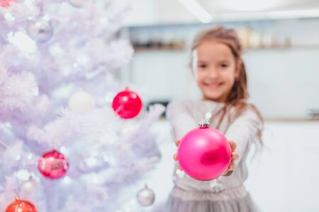 Pretty little girl is extending a pink bauble to the camera, standing near Christmas tree, smiling.