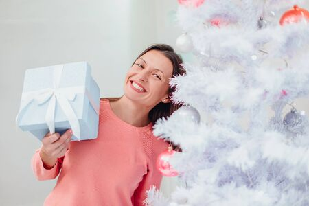 A shot of happy mom, finding a present for herself under christmas tree and now looks at it, smiling and feeling thankful.