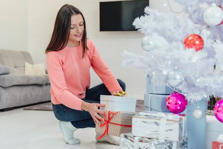 Attentive mother is preparing presents for children on winter holidays, putting them under the firtree. Stok Fotoğraf