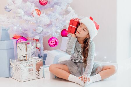 Cute child sitting in lotos position with a Christmas present in hand, holding box near ear, listening to what is inside.